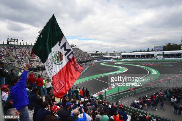 A fan of Sahara's Force India F1 Team Mexican driver Sergio Perez holds a Mexican national flag during the Formula One Mexico Grand Prix practice...