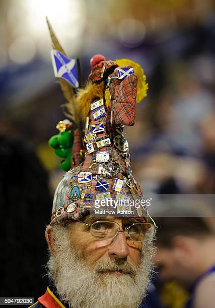 A fan of Scotland wearing a Loch Ness Monster hat covered in badges