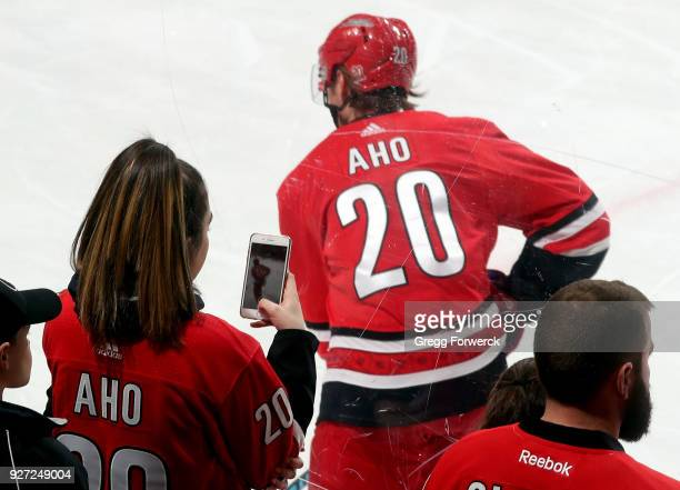 A fan of Sebastian Aho of the Carolina Hurricanes snaps his picture prior to an NHL game against the Winnipeg Jets on March 4 2018 at PNC Arena in...