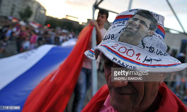 A fan of Serbian tennis player Novak Djokovic wears a hat with his picture during a welcoming ceremony in front of the Serbian National Assembly in...