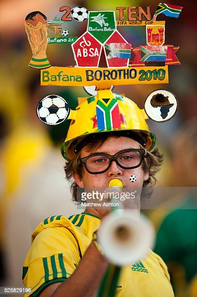 A fan of South Africa blowing a Vuvuzela and wearing a Makaraba football hat