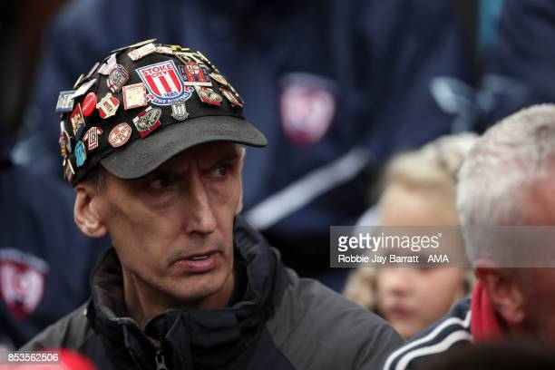 A fan of Stoke city wears a Stoke City cap covered in pin badges during the Premier League match between Stoke City and Chelsea at Bet365 Stadium on...
