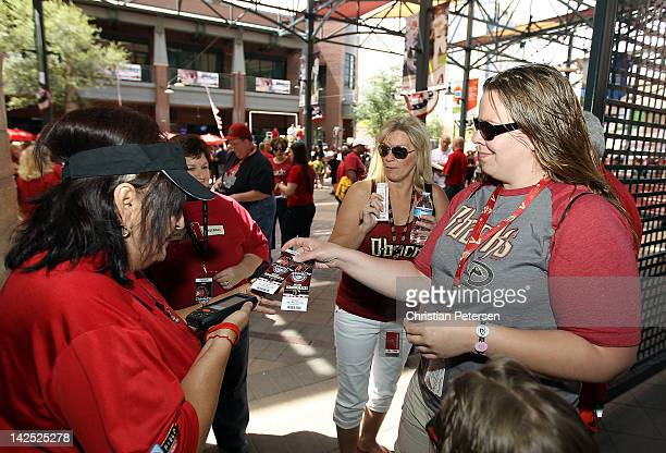 Fan of the Arizona Diamondbacks Renee Ross of Mes AZ gives her ticket as she arrives to the Opening Day game against the San Francisco Giants at...