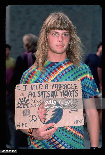 A fan of the band Grateful Dead holds a handmade sign reading I need a miracle hoping to get tickets to a Grateful Dead show