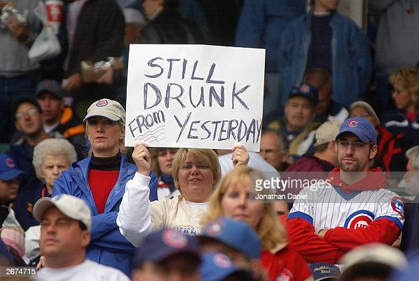 A fan of the Chicago Cubs holds up a sign reading Still Drunk from Yesterday in reference to the party held by fans after the Cubs clinched the...