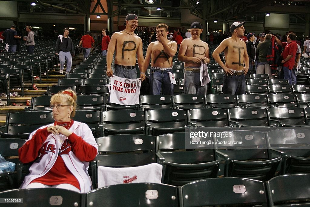 A fan of the Cleveland Indians sits dejected as fans of the Boston Red Sox look on during Game Five of the American League Championship Series at Jacobs Field on October 18, 2007 in Cleveland, Ohio. The Red Sox defeated the Indians 7 to 3.