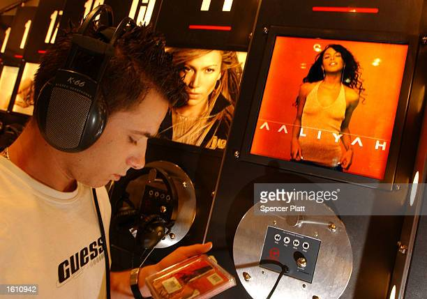 A fan of the former rhythmandblues singer and actress Aaliyah listens to the new Aaliyah album August 27 2001 at a Virgin Megastore in New York City...