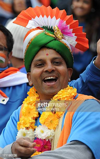 A fan of the Indian cricket team wearing a turban in the team's colours smiles as rain interupts the start of the 2013 ICC Champions Trophy Final...