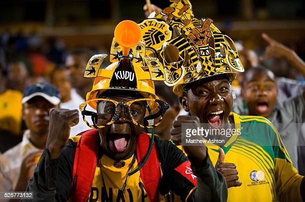 A fan of the Kaizer Chiefs wearing a makarapa a customised miner's hard hat / fan helmet and a pair of glasses