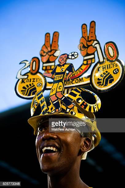 Fan of the Kaizer Chiefs wearing a makarapa a customised miner's hard hat / fan helmet