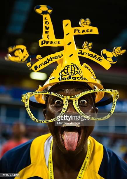 A fan of the Kaizer Chiefs wearing a makarapa a customised miner's hard hat / fan helmet wearing glasses