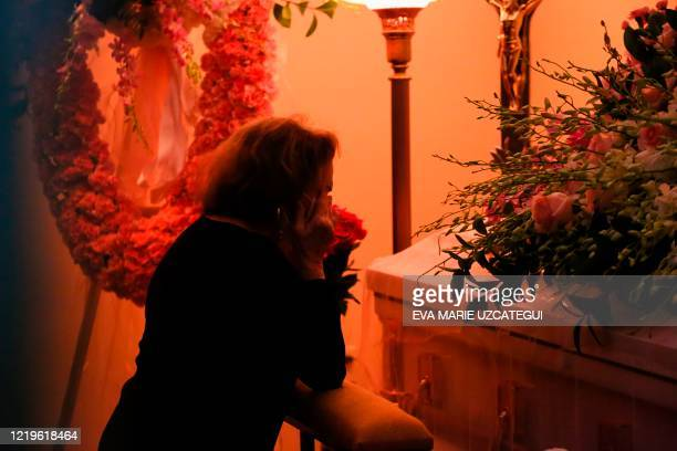 Fan of the late Cuban American singer and film actress Rosita Furnes kneels in front of her coffin during the funeral at Auxiliadora Funeria Nacional...