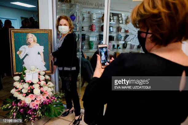 Fan of the late Cuban American singer and film actress Rosita Furnes poses for a photo in front of her portrait during the funeral at Auxiliadora...