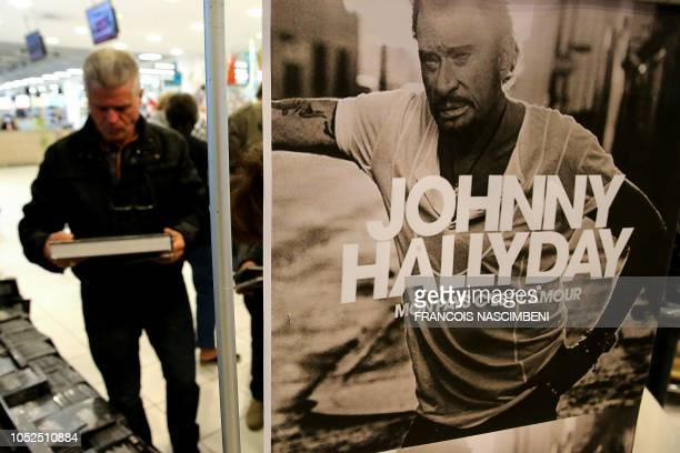 A fan of the late French singer Johnny Hallyday looks at Johnny Hallyday merchandising items on the day of the release of his posthumous album Mon...