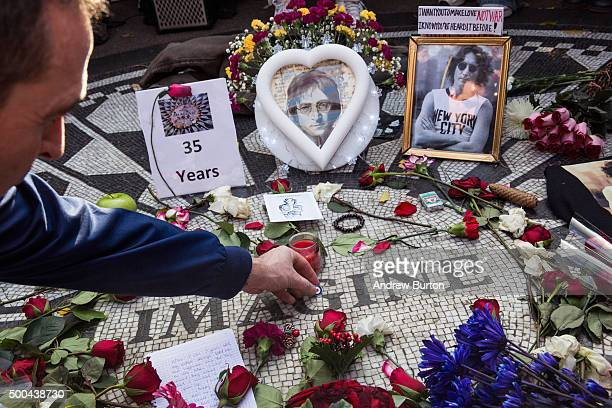 A fan of the late John Lennon places a pin a top the Strawberry Fields tile mosaic in Central Park which was created in tribute to the musician to...