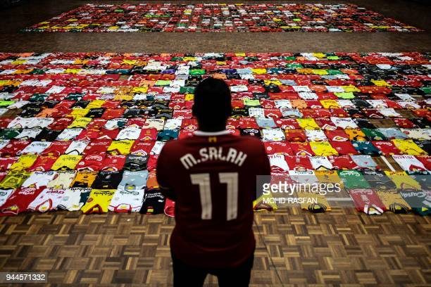 TOPSHOT A fan of the Liverpool football team stands infront of the 1278 jerseys displayed side by side on the floor during the Malaysia Book of...