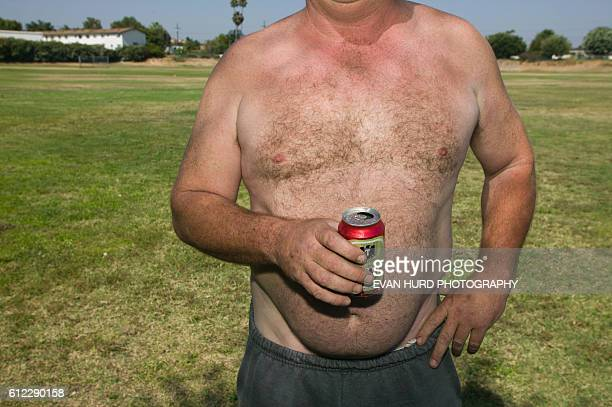 A fan of the Los Angeles Cricket team British Dominion drinks a beer and shows off his beer belly during a game in Buena Park Los Angeles