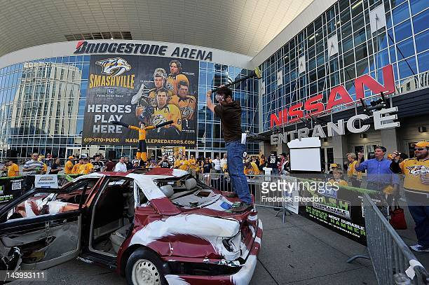 A fan of the Nashville Predators hits a car decorated like the Phoenix Coyotes with a sledgehammer prior to Game Four of the Western Conference...