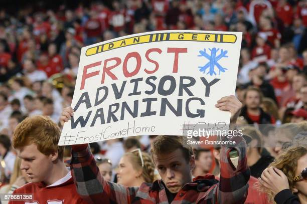 A fan of the Nebraska Cornhuskers holds a sign in support of coaching prospect Scott Frost during the game against the Iowa Hawkeyes at Memorial...