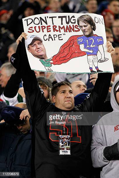A fan of the New England Patriots holds up a sign which reads Don't Tug on Superman's Cape in reference to Tom Brady of the New England Patriots and...