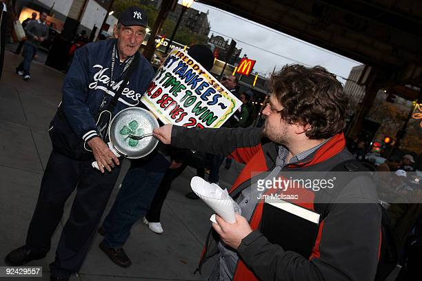 A fan of the New York Yankees talks with Freddy Sez outside the stadium prior to Game One of the 2009 MLB World Series against the Philadelphia...