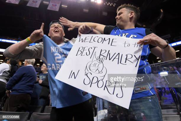 A fan of the North Carolina Tar Heels and the Duke Blue Devils hold a sign referring to the Duke/UNC rivalry during the semifinals of the ACC...