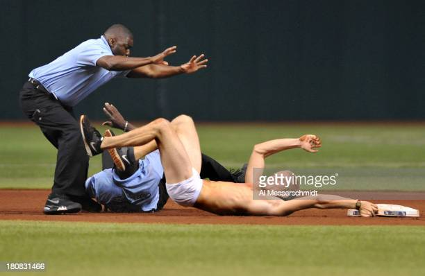 A fan of the Tampa Bay Rays attempts to steal second base and is tackled by a security guards in the 5th inning during play against the Texas Rangers...