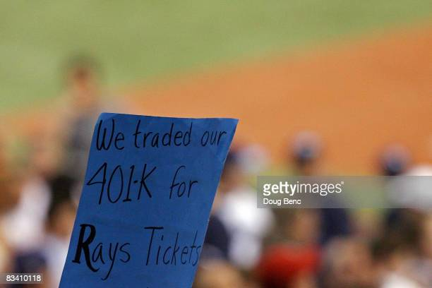 """Fan of the Tampa Bay Rays holds up a sign which reads """"We traded our 401k for Rays Tickets"""" against the Philadelphia Phillies during game two of the..."""