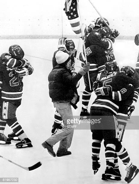 Fan of the U.S ice hockey team, carrying the national flag, walks among the players as they embrace each other following their victory over Finland...