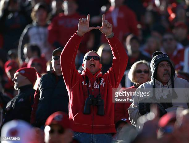 A fan of the Utah Utes makes a U with his fingers at a game against the UCLA Bruins during the first half of a college football game at Rice Eccles...