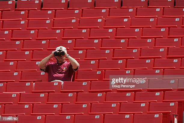 A fan of the Washington Redskins looks through binoculars during NFL week one against the Tampa Bay Buccaneers at FedEx Field on September 12 2004 in...