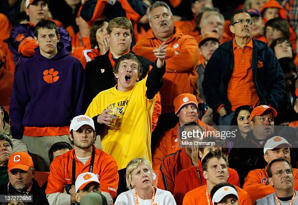 A fan of the West Virginia Mountaineers laughs as fans of the Clemson Tigers look on dejected late in the second quarter during the Discover Orange...