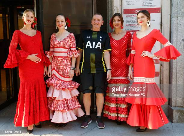 A fan of Tottenham Hotspur poses with poses with girls dressed in typical flamenco dress ahead of the UEFA Champions League final between Tottenham...