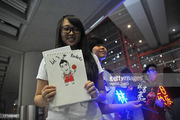A fan of US NBA player Jeremy Lin displays a cartoon of Lin as she waits for his arrival at an airport in Beijing on August 23 2013 Lin is on a visit...