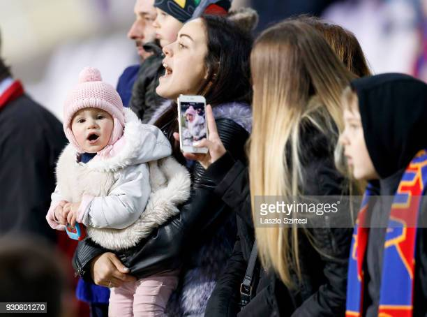 Fan of Vasas FC holds his little daughter in her arms while an other fan takes a photo from the baby during the Hungarian OTP Bank Liga match between...