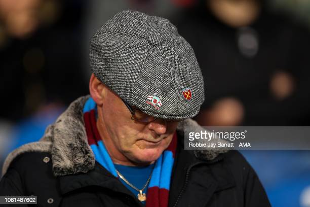 A fan of West Ham United wearing a flat cap with pin badges on during the de4d54221fa