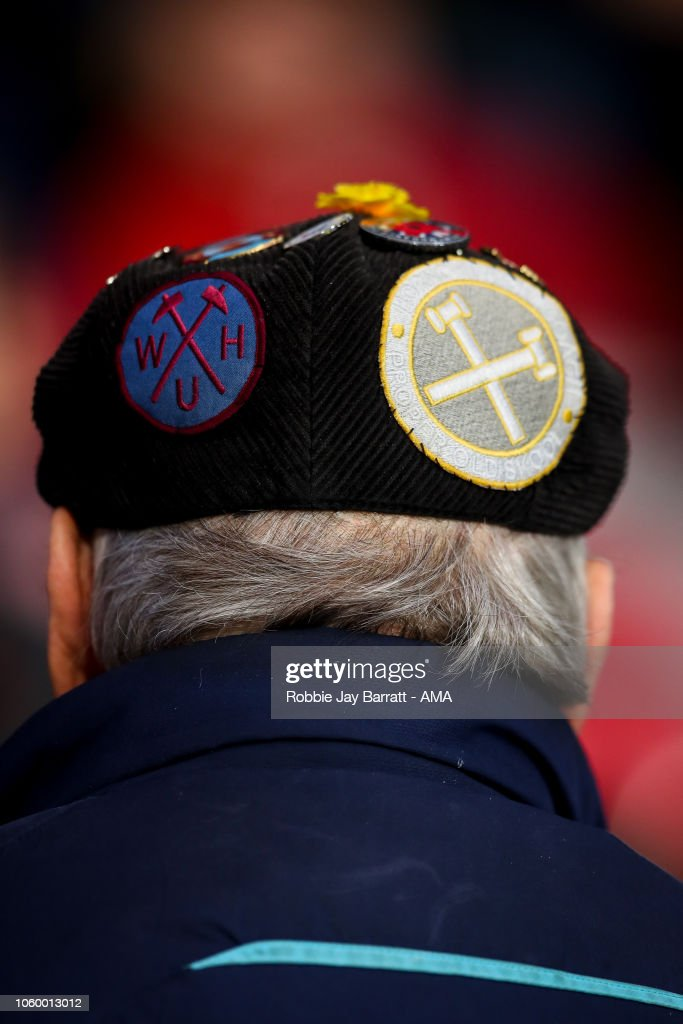 A fan of West Ham United wears a flat cap with pin badges on during ... 07d826ee48c