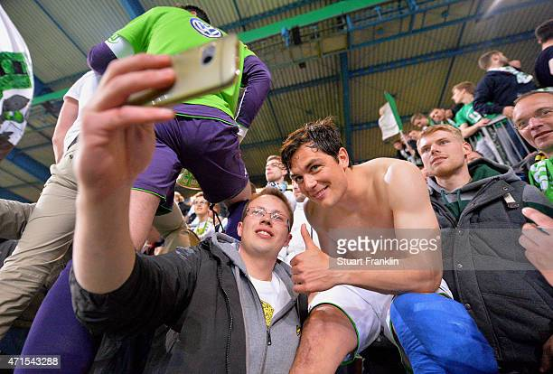 A fan of Wolfsburg takes a selfie with Marcel Schaefer of Wolfsburg after the DFB Cup Semi Final match between Arminia Bielefeld and VfL Wolfsburg at...