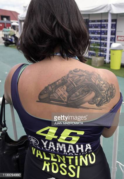 Fan of Yamaha's Italian biker Valentino Rossi, shows a tattoo depicting him, as she waits for him at the pits on the eve of the Argentina Grand Prix...
