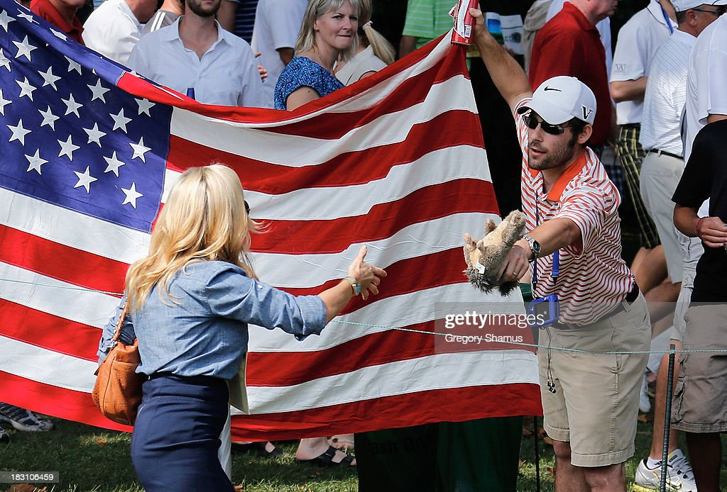 A fan offers a toy squirrel to Amy Mickelson of the U.S. Team on the second hole during the Day Two Foursome Matches at the Muirfield Village Golf Club on October 4, 2013 in Dublin, Ohio.