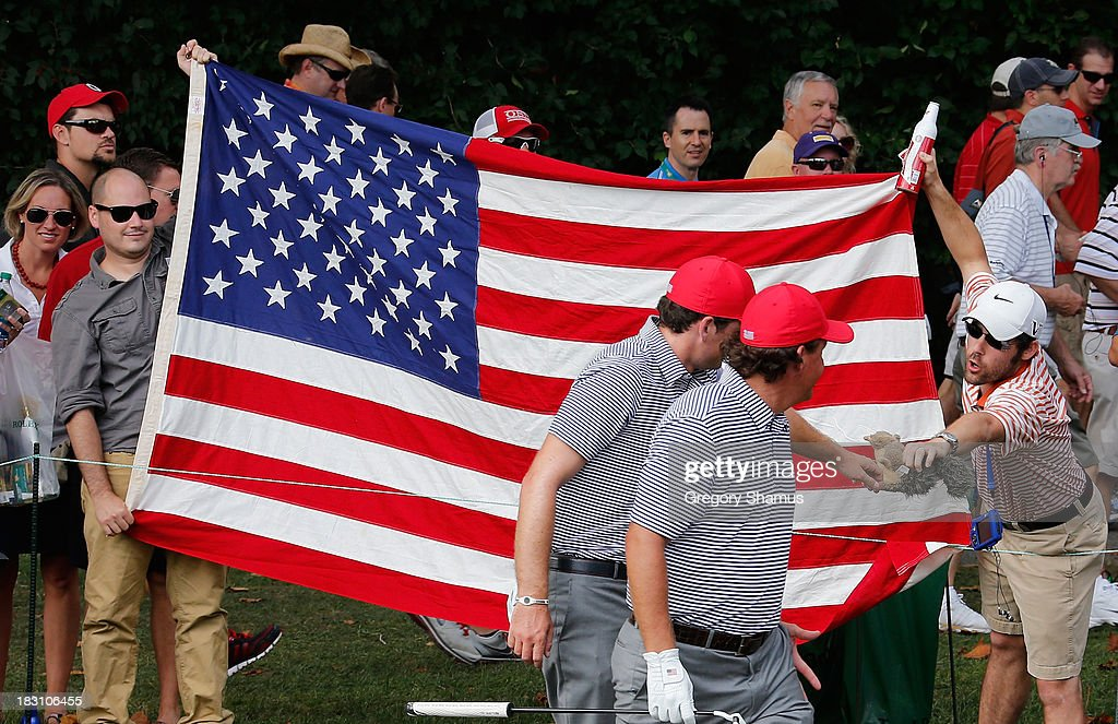 A fan offers a toy squirrel to Keegan Bradley (L) and Phil Mickelson of the U.S. Team on the second hole during the Day Two Foursome Matches at the Muirfield Village Golf Club on October 4, 2013 in Dublin, Ohio.