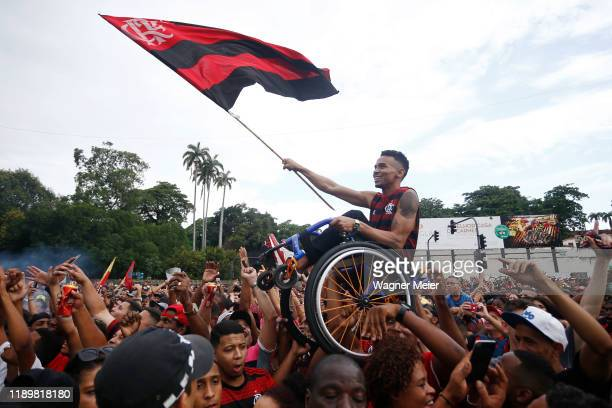 A fan on a wheelchair is lifted as he waves a flag during the celebrations the day after Flamengo won the Copa CONMEBOL Libertadores on November 24...
