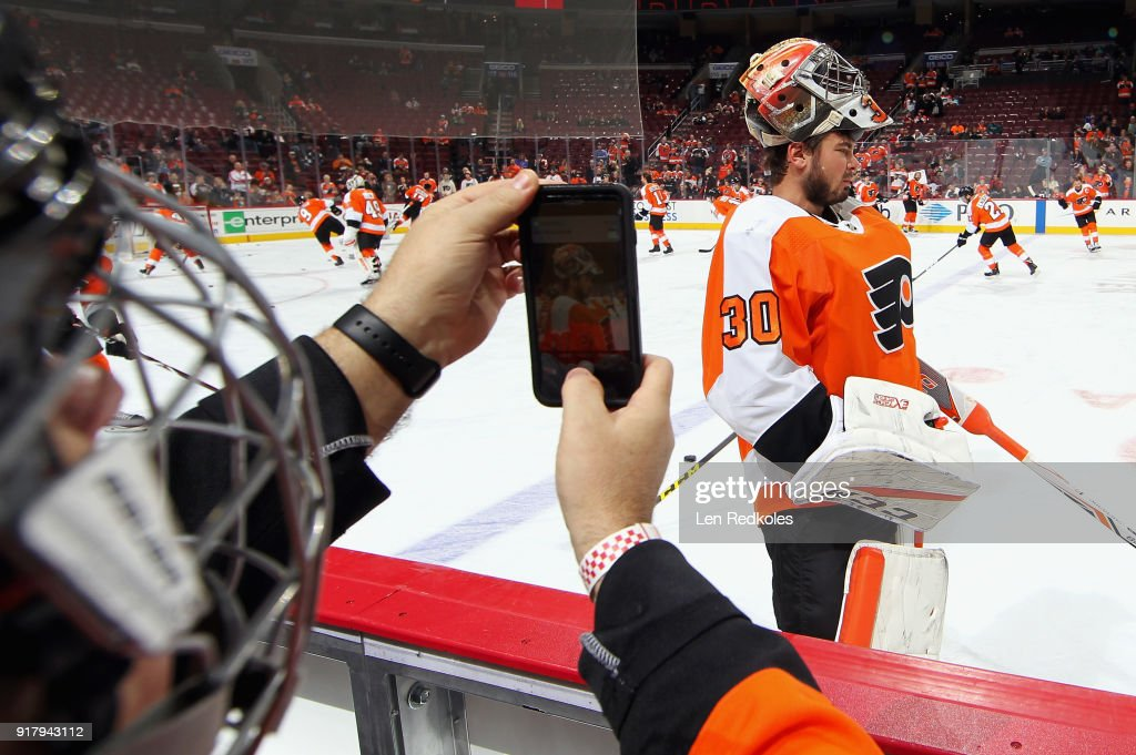 A fan on the bench takes a photo of Michal Neuvirth #30 of the Philadelphia Flyers during warmups prior to this evening's game against the New Jersey Devils on February 13, 2018 at the Wells Fargo Center in Philadelphia, Pennsylvania.