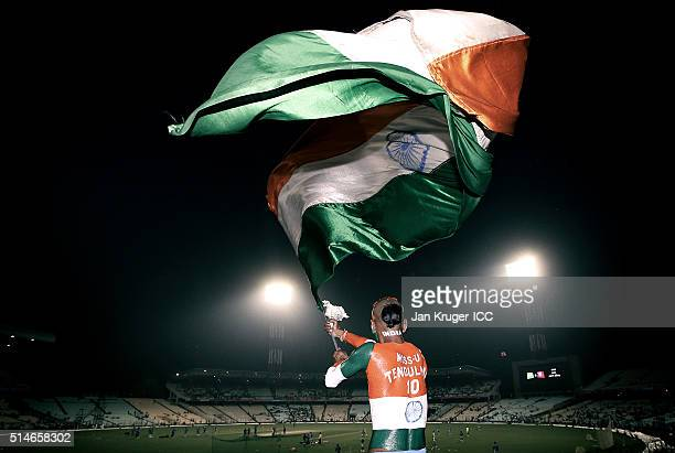 A fan painted in the Indian colours waves his flag during the ICC World Twenty20 warm up match between India and West Indies at Eden Gardens on March...