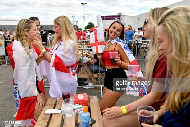 Fan paints her friends face at the 4TheFans Secret City fan zone at Event City on June 13, 2021 in Manchester, England. Fanzones and pubs are hosting...