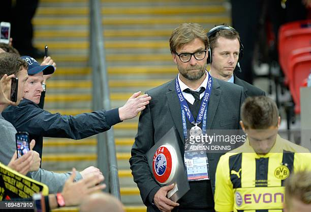A fan pats Borussia Dortmund's Head Coach Juergen Klopp on the shoulder after his teaqm lost the UEFA Champions League final football match between...
