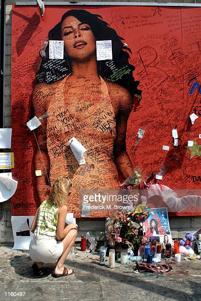 A fan pauses by a shrine to the singer Aaliyah on Sunset Boulevard August 31 2001 in Los Angeles CA The singer died a week earlier in a plane crash...