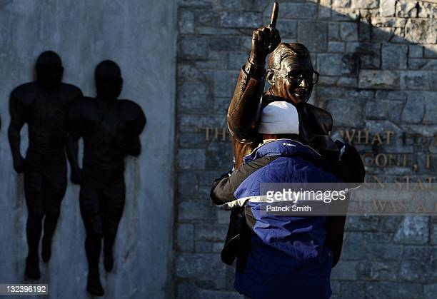 A fan pays respect to a statue of former Penn State football coach Joe Paterno before the Penn State against Nebraska football game at Beaver Stadium...