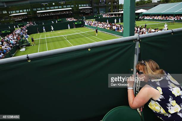 A fan peaks through a gap in the fence to watch the tennis action on day one of the Wimbledon Lawn Tennis Championships at the All England Lawn...