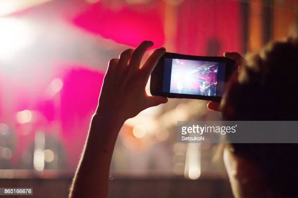 fan photographing through smart phone while enjoying music concert - 特定できない人物 stock pictures, royalty-free photos & images